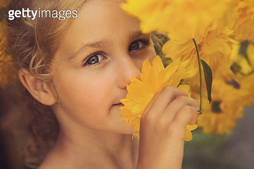 Girl smelling yellow flowers - gettyimageskorea