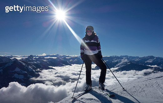 Young woman with ski equipment against Alps mountains, Austria, Europe - gettyimageskorea