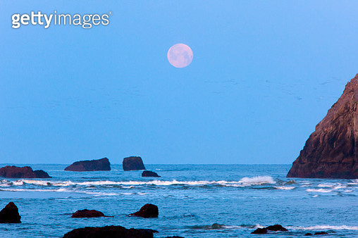 Moon set over rock formations at low tide, Bandon Beach, Oregon, USA - gettyimageskorea