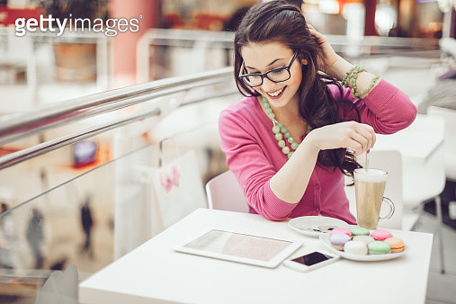 Young woman reading tablet and drinking latte in a cafe - gettyimageskorea