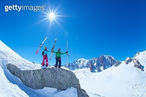 Male and female skiers holding up skis on Mont Blanc massif, Graian Alps, France - gettyimageskorea