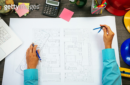 Image of architect measuring and altering blueprint - gettyimageskorea
