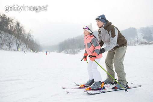 Young father teaching daughter to ski - gettyimageskorea