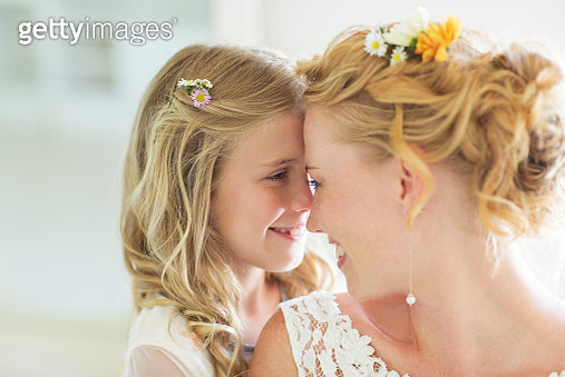 Bride and bridesmaid facing each other smiling - gettyimageskorea