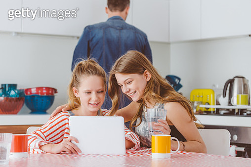 Teenage sisters using a digital tablet in kitchen at home - gettyimageskorea