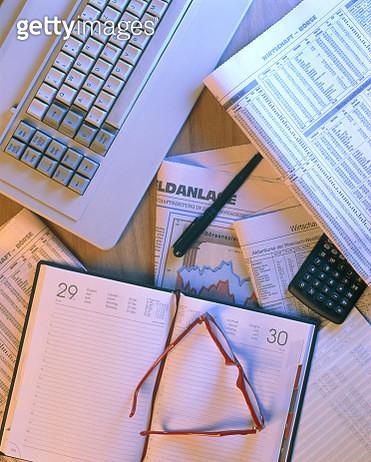 Keyboard, agenda, financial newspaer, glasses, pen and calculator - gettyimageskorea