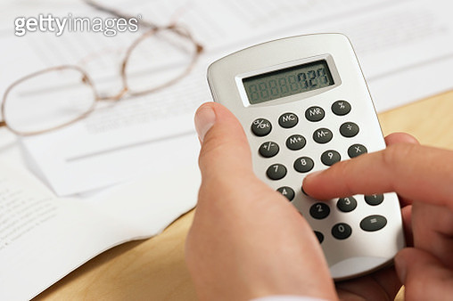 Businessman using calculator - gettyimageskorea