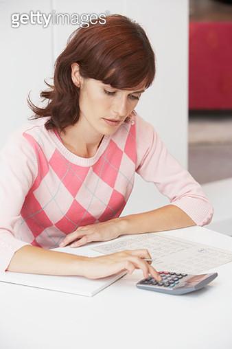 Woman using calculator - gettyimageskorea