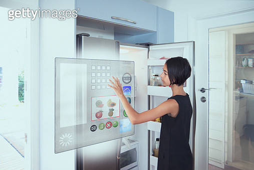 Mixed race girl using hologram refrigerator touch screen in kitchen - gettyimageskorea