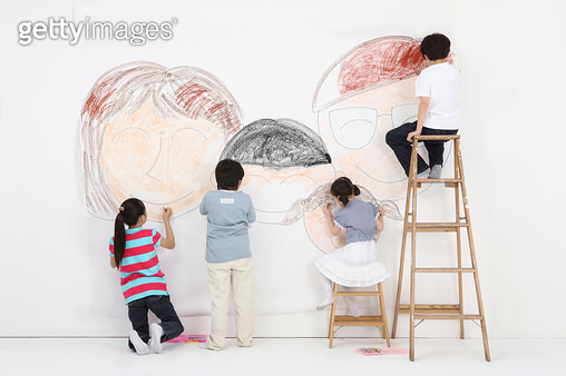 Children drawing faces on wall - gettyimageskorea