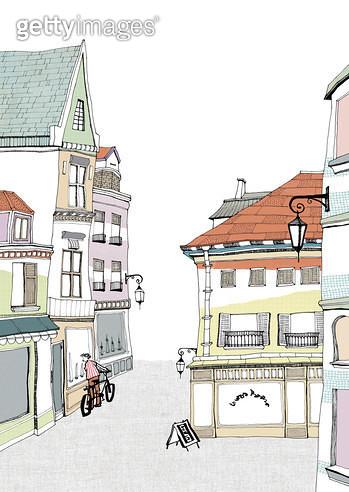 유럽의 한적한 골목길의 자전거타고 가던 남자가 있는 풍경 - gettyimageskorea