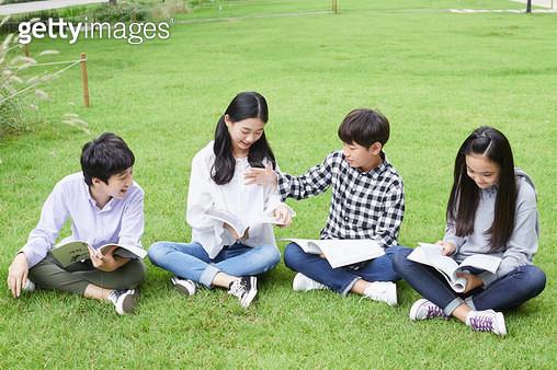 잔디에 앉아 책을 읽는 아이들 - gettyimageskorea