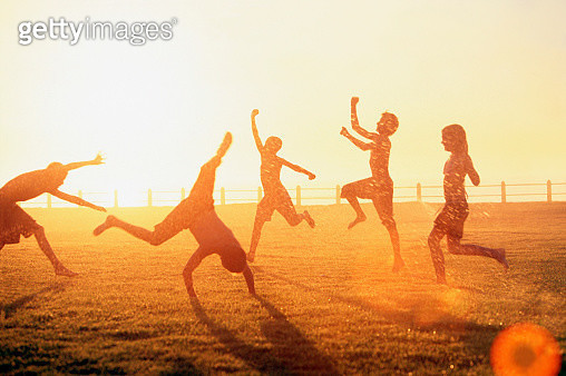 Children Playing in Sprinkler - gettyimageskorea