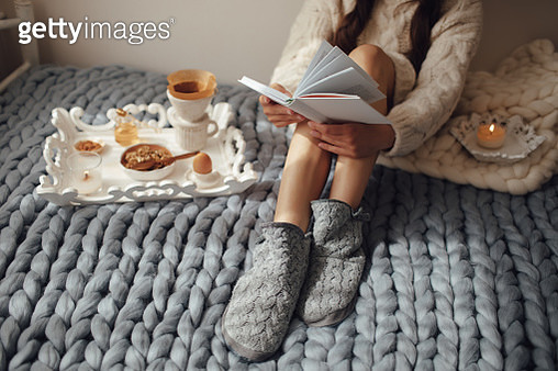Woman with long hair drinking hot coffee and reading book in bed. Woman in woolen socks and sweater sitting on wool chunky merino plaid. Cozy winter morning concept. - gettyimageskorea