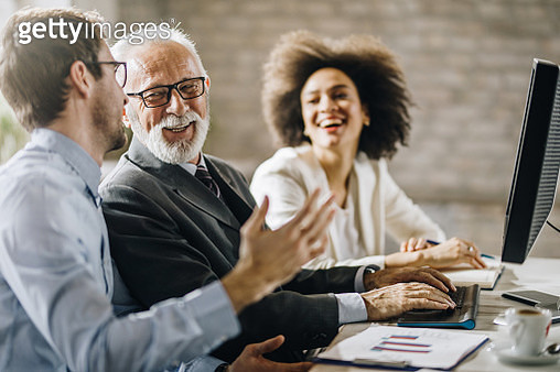 Happy business colleagues talking while working on PC in the office. - gettyimageskorea