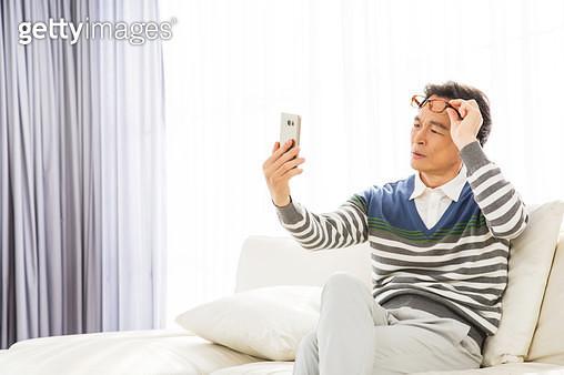 노안으로 스마트폰을 멀리보는 중년남성 - gettyimageskorea