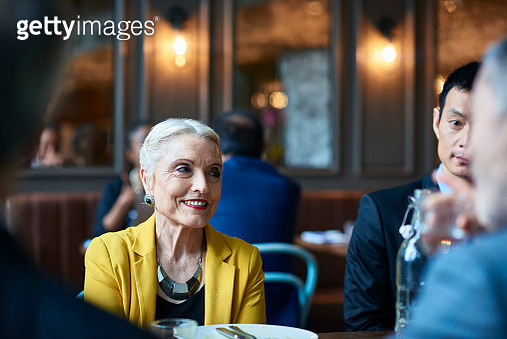 Senior businesswoman smiling and looking away during dinner - gettyimageskorea