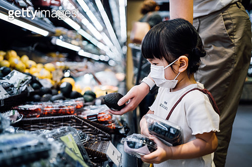 Cute little Asian girl with protective face mask grocery shopping with her mother in a supermarket. They are choosing fresh organic blueberries and avocados in the produce aisle - gettyimageskorea