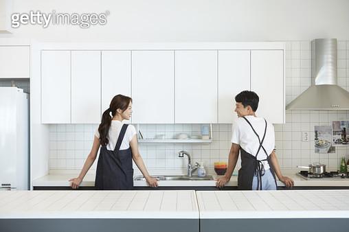 앞치마를 한 젊은부부가 주방의 싱크대를 두손으로 짚고 서서 서로를 마주보며 웃는 뒷모습 - gettyimageskorea