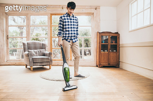 청소기로 거실을 청소하는 남자 - gettyimageskorea