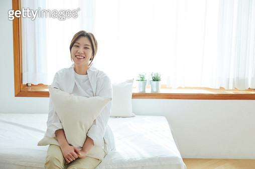 침대에 앉아 있는 여자 - gettyimageskorea