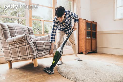 청소기로 의자밑을 청소하는 남자 - gettyimageskorea