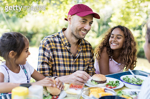 Happy father and daughters enjoying barbecue lunch - gettyimageskorea