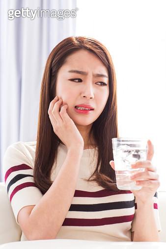 얼음물을 마시며 치통을 느끼는 여성 - gettyimageskorea