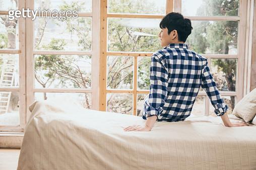 침대에 앉아 창밖을 바라보는 남자 뒷모습 - gettyimageskorea