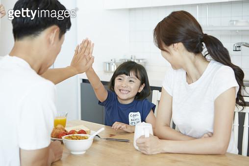 아침식사 중에 식탁을 사이에 두고 하이파이브하는 딸과 아빠 - gettyimageskorea
