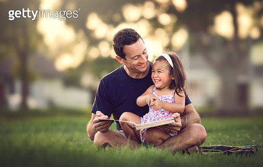 A smiling middle aged dad reads a silly story to his laughing 2 year old daughter at the park in front of his home. - gettyimageskorea