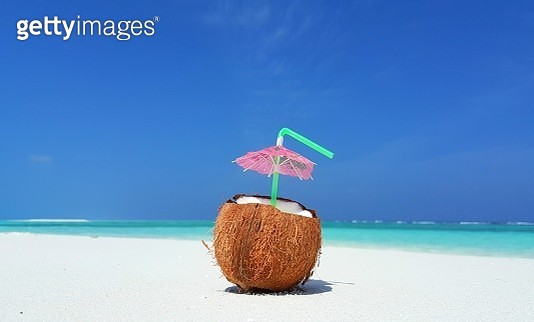 Fresh coconut juice on the white sand with blue water and clear sky in the Background in Maldives - close-up shot - gettyimageskorea
