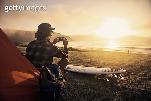 Shot of a surfer by his tent while waiting for the perfect wave - gettyimageskorea