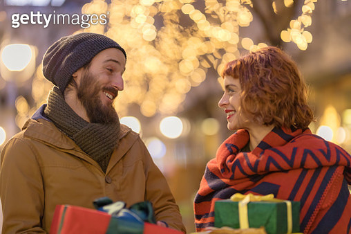 A happy smiling couple in love holding gifts on the street - gettyimageskorea