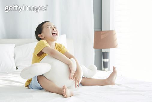 침대에 앉아 인형을 안고 크게 웃는 여자어린이 - gettyimageskorea