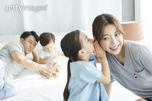 엄마에게 귓속말을 하는 딸, 침대 위의 젊은가족 - gettyimageskorea
