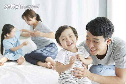 아빠와 즐겁게 웃는 어린 아들, 침대 위의 젊은가족 - gettyimageskorea