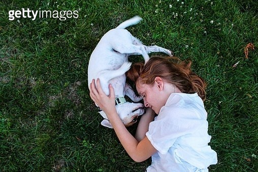 Little redheaded girl lying in the grass on her side with her little white dog. The shot is taken from above looking directly down on them. It's a waist up crop. The little girl and the dog are nose to nose. They are making a circle shape in the photograp - gettyimageskorea