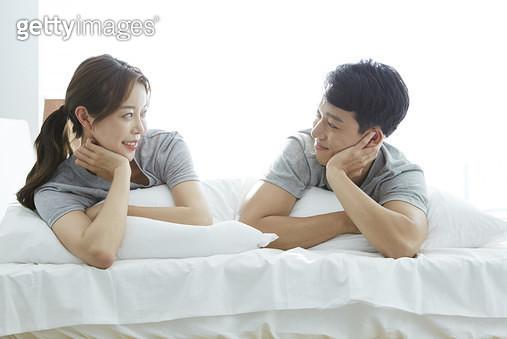 침대에 엎드려 서로를 마주보는 젊은부부 - gettyimageskorea