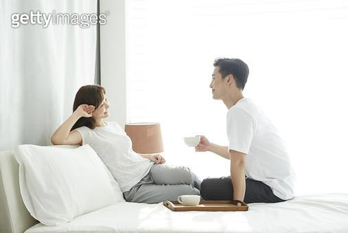 침대에 앉아 차를 마시며 대화하는 젊은부부 - gettyimageskorea