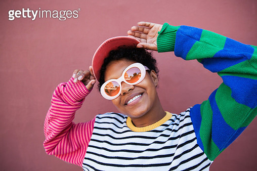 A young woman wearing pink sunglasses and a colorful outfit smiling at the camera - gettyimageskorea