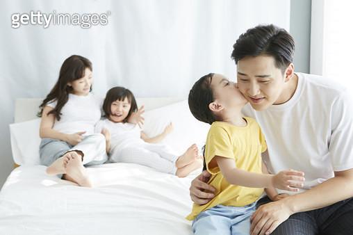 아빠에게 귓속말을 하는 딸, 침대 위의 젊은가족 - gettyimageskorea