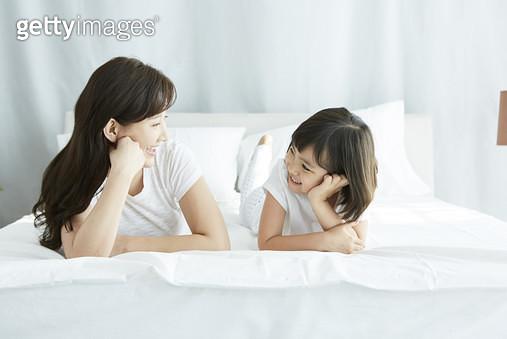 침대 위에 엎드려서 턱을 괴고 마주보며 웃는 엄마와 딸 - gettyimageskorea