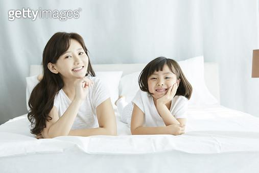 침대 위에 엎드려서 턱을 괴고 앞을 보며 웃는 엄마와 딸 - gettyimageskorea