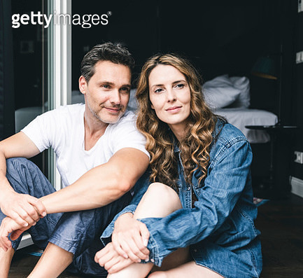 Smiling couple in nightwear at home sitting at French window - gettyimageskorea