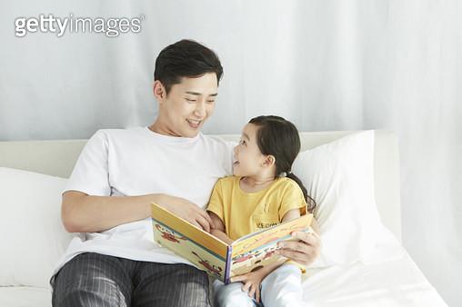 침대 위에 앉아서 딸에게 책을 읽어주는 다정한 아빠의 모습 - gettyimageskorea