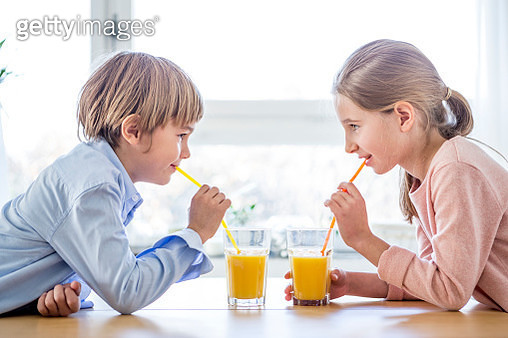 Brother and sister drinking orange juice - gettyimageskorea