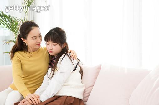 쇼파에 앉아 있는 엄마와 우울한 딸 - gettyimageskorea