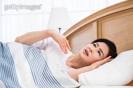 자면서 더워하는 중년여성 - gettyimageskorea