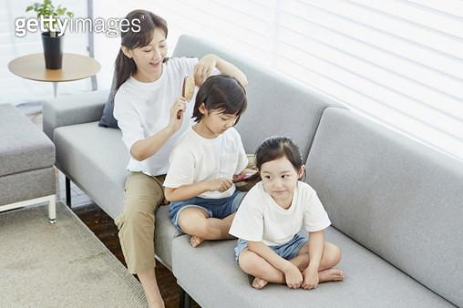 거실 소파에 일렬로 앉아 머리를 빗는 엄마와 딸들 - gettyimageskorea